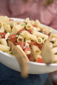 Person holding bowl of pasta salad with tomatoes & olives