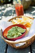 Guacamole with tortilla chips in a basket, tomato drink