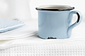 Coffee in blue cup on white tea towel