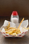 Chips in cardboard container, salt shaker behind
