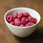 Fresh raspberries in a small ceramic bowl