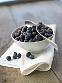 Fresh blueberries in a small bowl with spoon