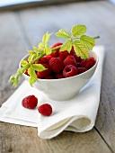 Fresh raspberries & raspberry branch in small bowl on napkin