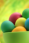 Coloured eggs in green bowl