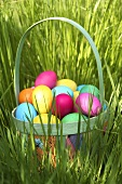 Basket of coloured eggs in grass