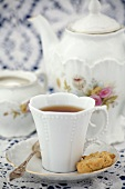 A cup of black tea with teapot, sugar bowl and biscuit