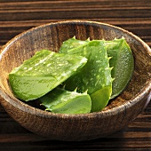 Pieces of Aloe vera leaves in wooden bowl