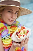 Woman holding shell full of fresh fruit by sea