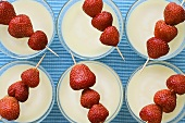 White strawberry soup with skewered strawberries