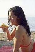 Junge Frau am Strand mit Orange in der Hand