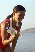 Young woman working out with a bottle of water in her hand