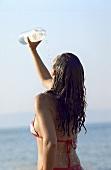 Junge Frau übergiesst sich mit Wasser