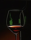 A glass of red wine with a projected image of a vine leaf