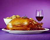 Roast goose with red cabbage, potato dumplings & red wine