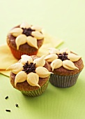 Three orange nut muffins with orange cream & chocolate sprinkles