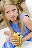 Blond girl eating hot dog