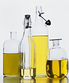 Various types of edible oils in bottles against white background