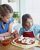 Two girls putting mozzarella on top of a pizza