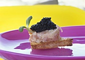 Toast triangle topped with salmon tartare and caviar