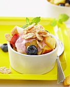 Fruit salad with berry yoghurt and cornflakes