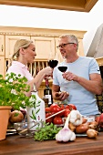 Kitchen scene: couple clinking glasses of red wine