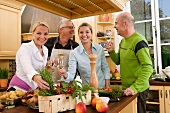 Two couples with glasses of white wine preparing food