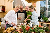 Two couples preparing food together