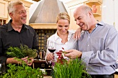 Friends in kitchen with herbs, chillies and red wine