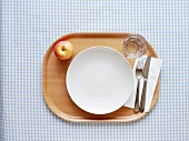 Empty plate, cutlery, glass and apple on tray