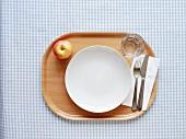 Tablett mit leerem Teller, Besteck, Wasserglas und Apfel