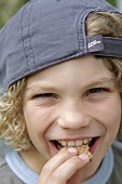 Boy in baseball cap eating wafer biscuit
