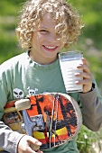 Boy with skateboard under his arm drinking a glass of milk