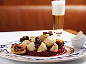 Potato dumplings with savoury filling on cranberry sauce