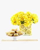 Lemon slices on cake stand and yellow freesias
