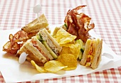Club sandwich with fried bacon and potato crisps
