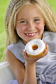 Blond girl eating doughnut