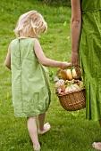 Kleines Mädchen trägt mit Mutter einen Picknickkorb