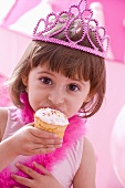 Little girl with a crown on her head eating a muffin