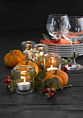 Pumpkins, rose hips, plates, tealights and wine glasses