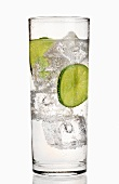 A glass of gin and tonic with slices of lime and ice cubes