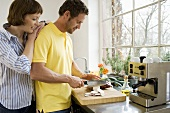 Man slicing vegetables, woman looking over his shoulder