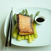 Teriyaki salmon on green asparagus with soy sauce