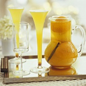Orange punch in carafe and two glasses