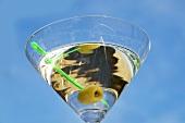 Martini mit Olive vor blauem Himmel