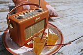 Picnic scene: glasses of juice & old radio on wooden planking