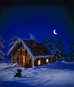 Illuminated gingerbread house in wintry landscape