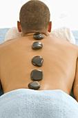 Mann mit warmen Steinen auf dem Rücken (Hot Stone Massage)