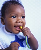Baby chewing a plastic spoon