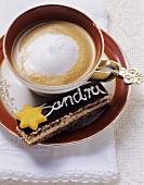 Cappuccino und schwarz-weiss-Gebäck (mit Schrift verziert)