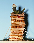 A tower of sausages and slices of white bread